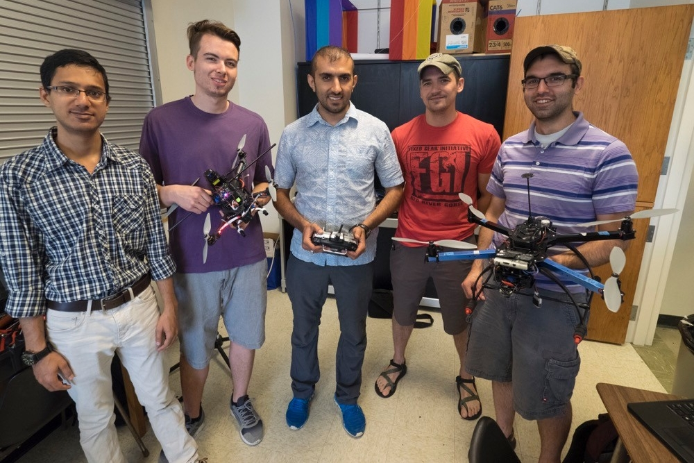 UC aerospace engineering students stand together holding hand made drones.