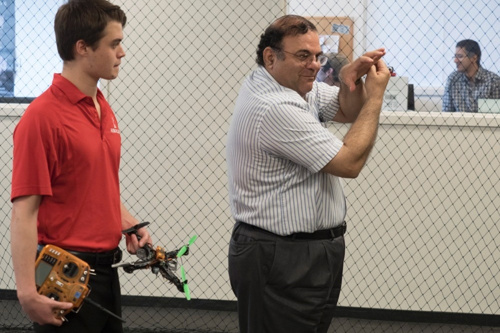 Kelly Cohen uses his hands to demonstrate how to operate a small drone to a student.