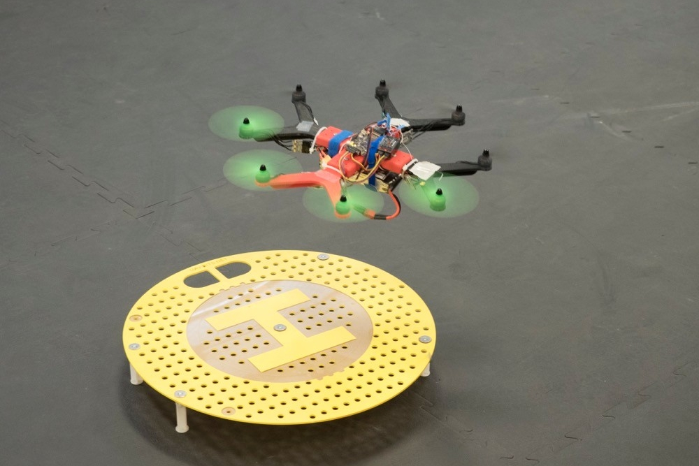 A small octocopter drone hovers over a landing circle.