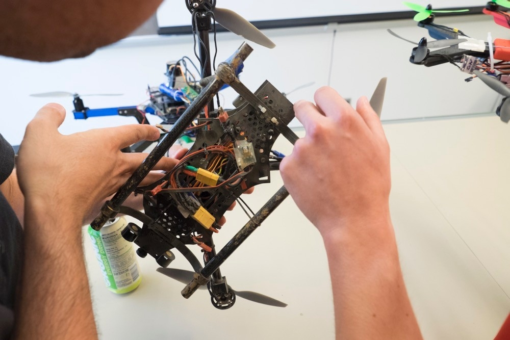 Close-up of UC students' hands as they explain the intricate parts within a four-rotor drone.