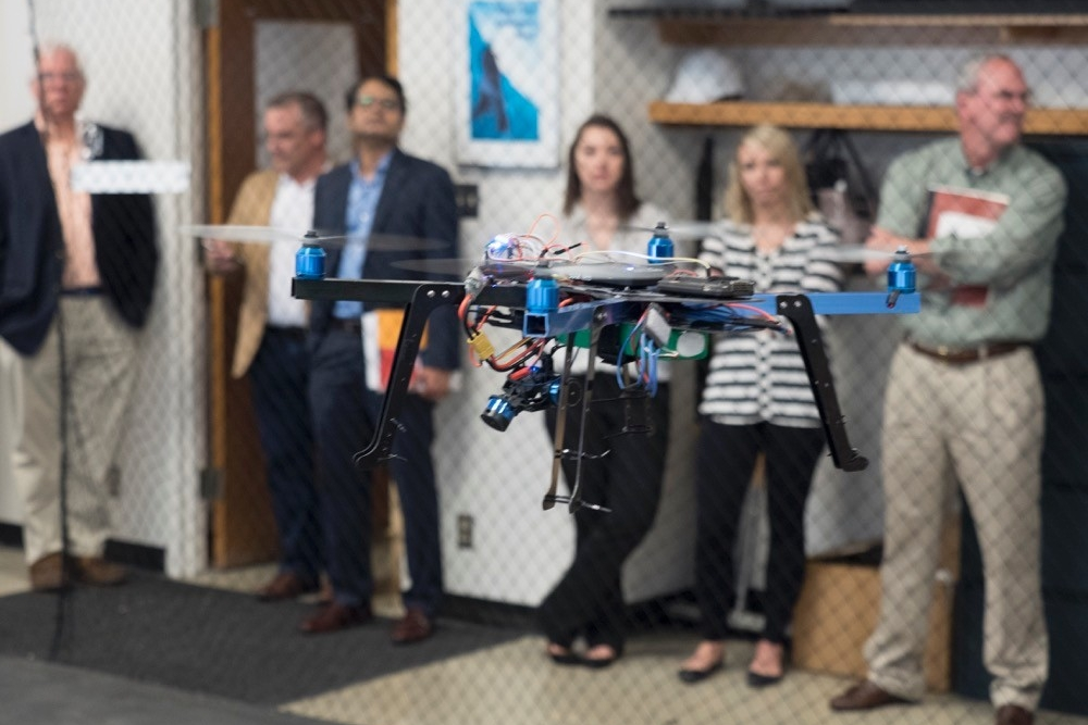 People look on as a small drone idles in the air in front of them.
