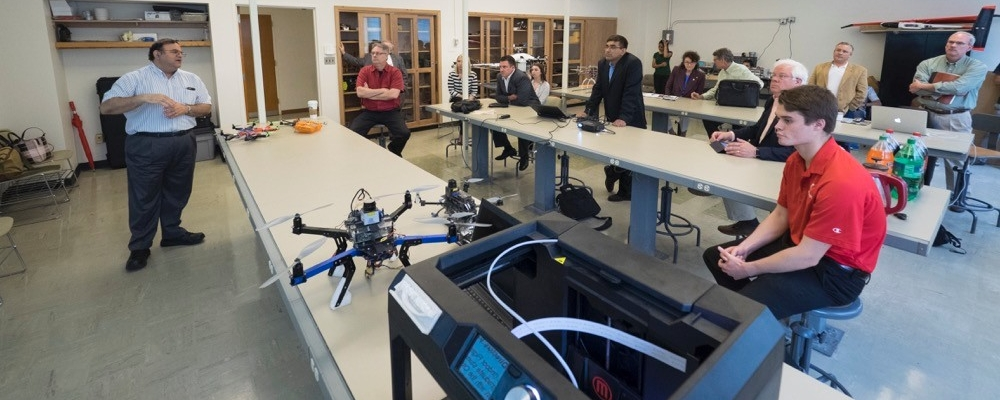 Kelly Cohen, UC professor of aerospace engineering speaks to a group in a room with UVA drones on display