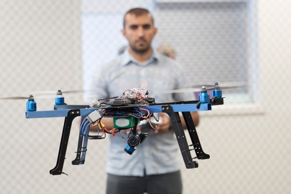 UC student operates a small drone in the air in front of him.