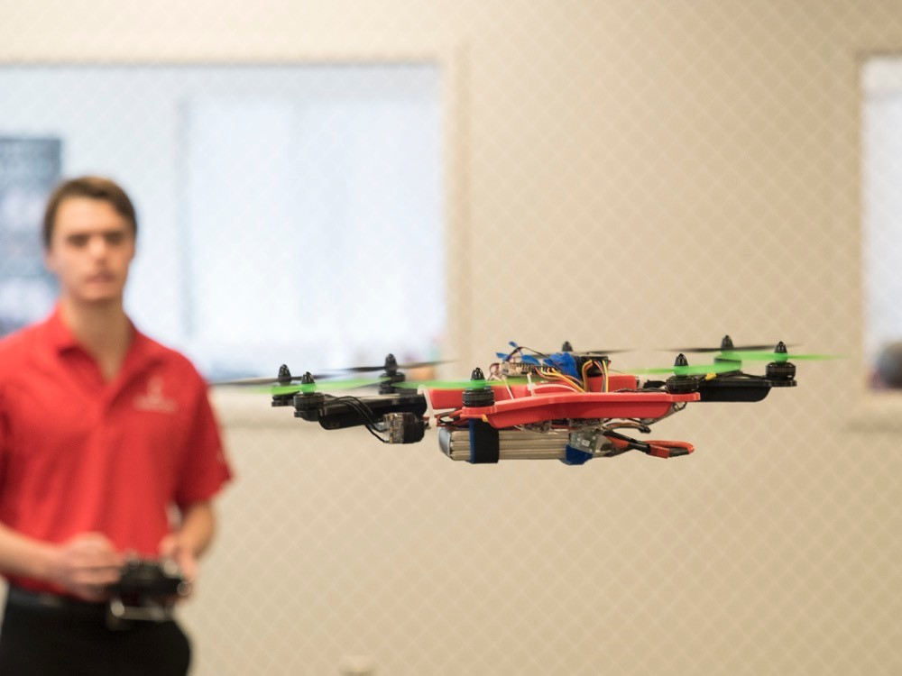 UC student stands in background as a four-rotor drone idles in the air in front of him