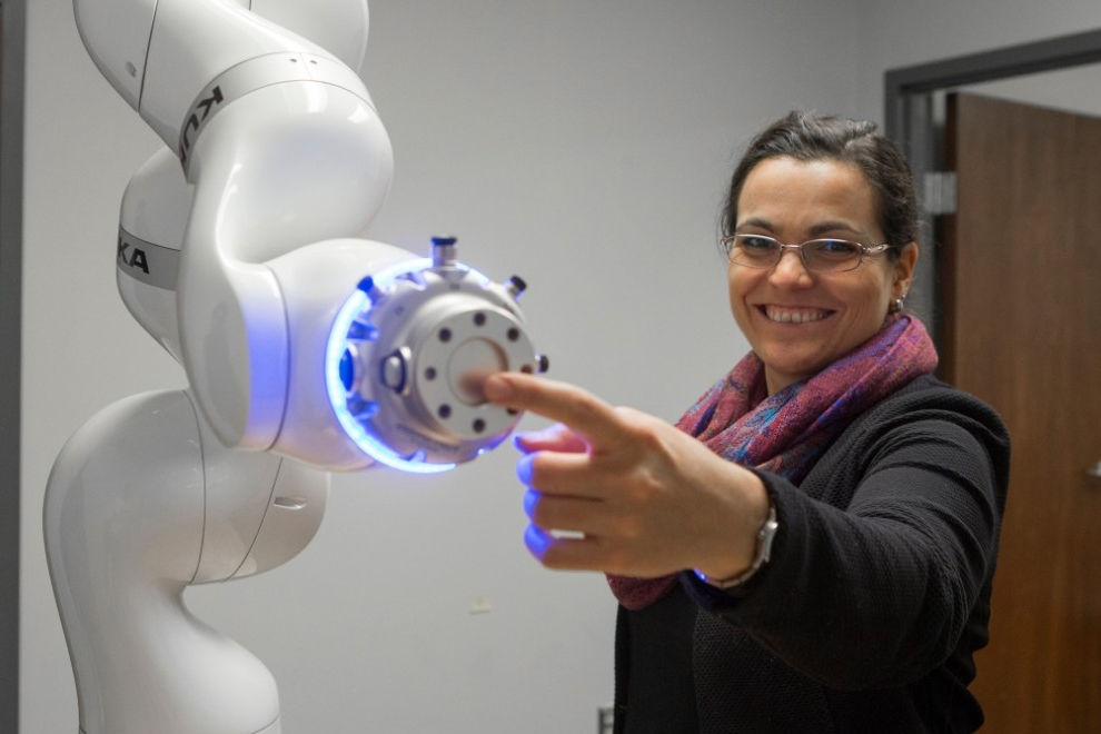 UC assistant professor Tamara Lorenz shows off Tess, a robot she uses in her psychology research.
