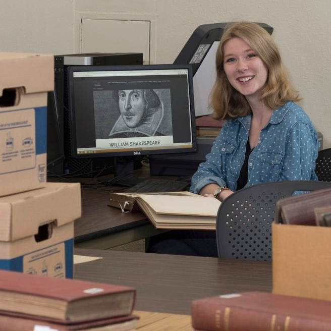 UC student Sydney Vollmer sits at her computer/scanner surrounded by books in UC's archives library.