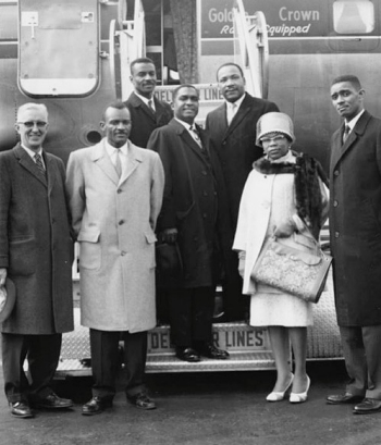 Louise Shropshire stands next to a train with civil rights leaders Rev. Maurice McCrackin, Rev. T.L. Lane, Rev. Fred Shuttlesworth Sr., Rev. Venchael L. Booth, Rev. Martin Luther King Jr., and Rev. Otis Moss Jr.