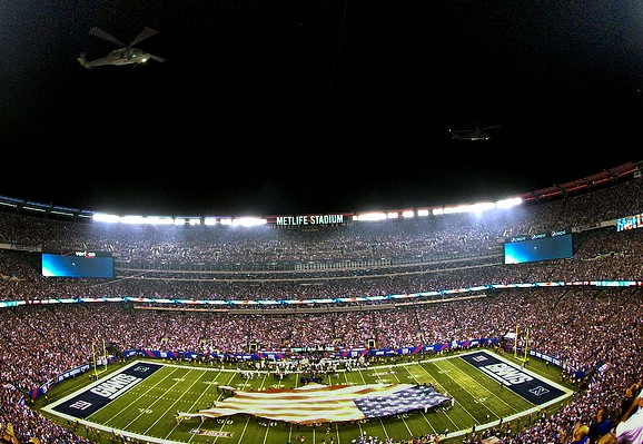 Military carry an American flag onto a football field