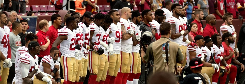 Several San Francisco 49ers kneel during the National Anthem before a game against the Washington Redskins at FedEx Field on October 15, 2017 in Landover, Maryland