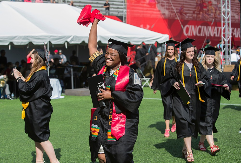 An especially emotional graduate celebrates after Commencement among other grads