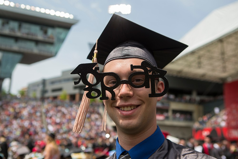 One student wears decorative glasses that say grad