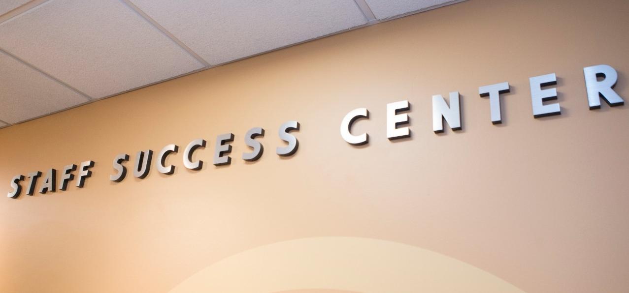 UC Staff Success Center sign along hallway wall.