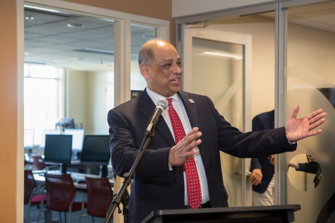 UC President Neville Pinto stands at the podium at the Staff Success Center ribbon cutting event.