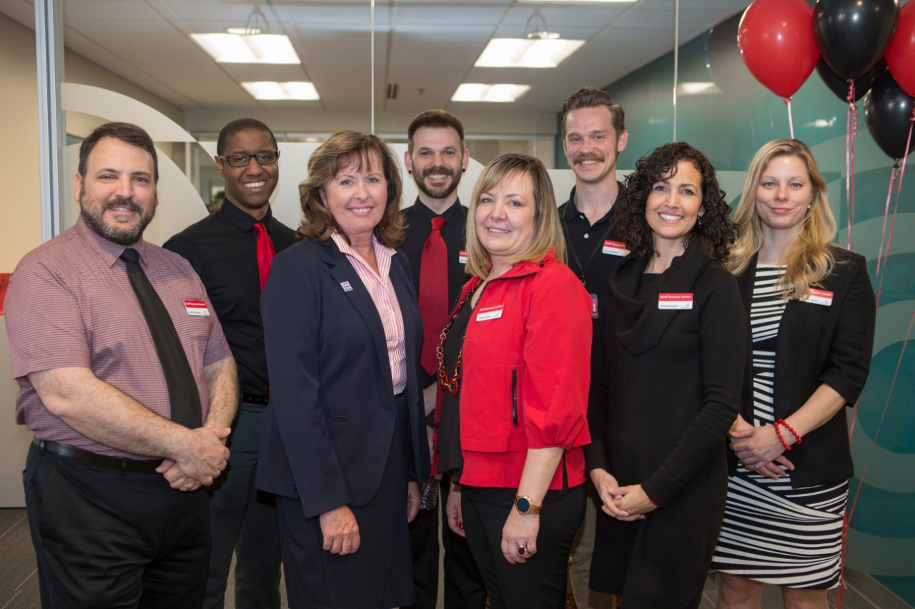 UC staff members stand together at the Staff Success Center ribbon cutting event.