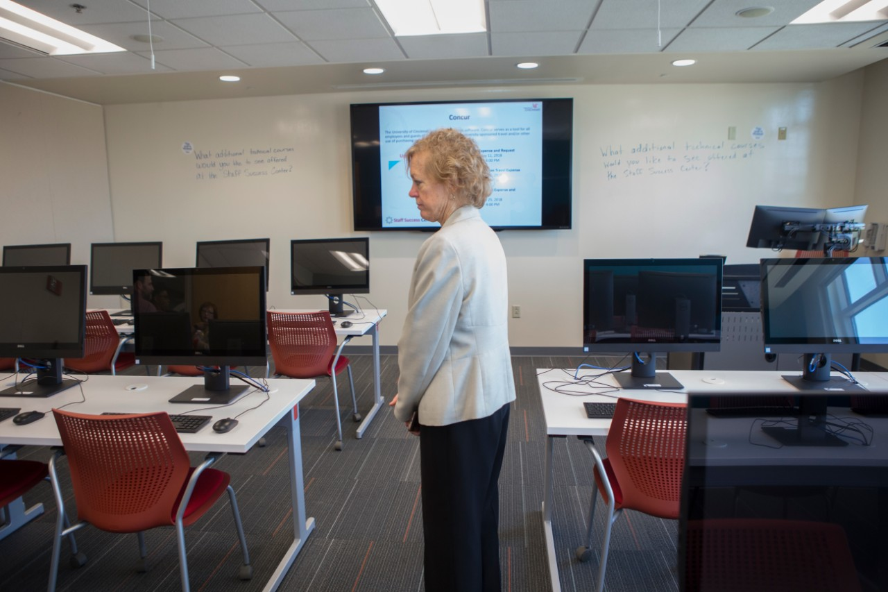 A UC staff member stands inside a room of computers at the Staff Success Center ribbon cutting event.
