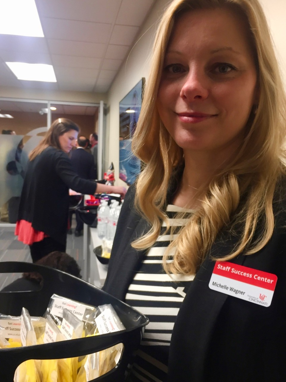 UC Staff Success Center's Michelle Wagner holds a basket of cookies at the ribbon cutting event.