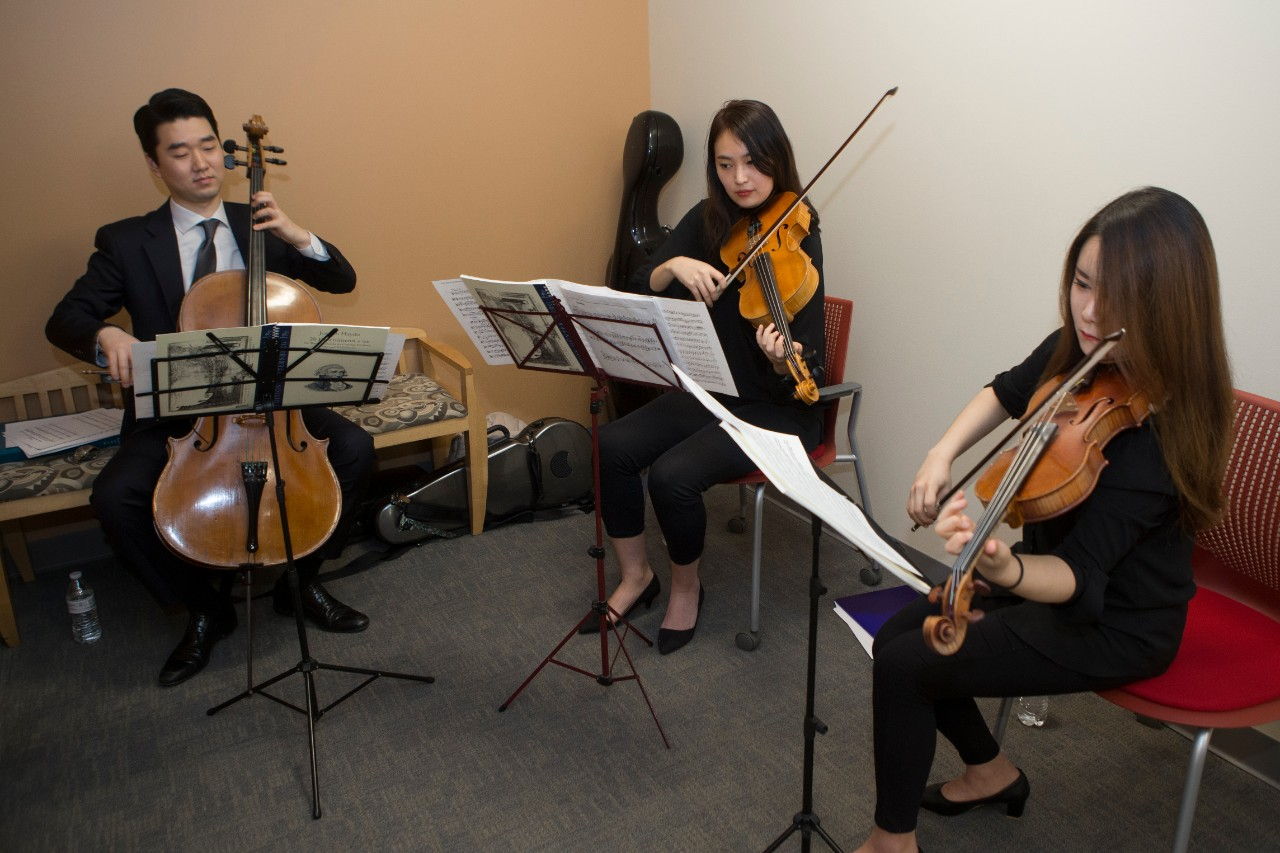 Members of CCM's chamber orchestra play at a ribbon cutting event.