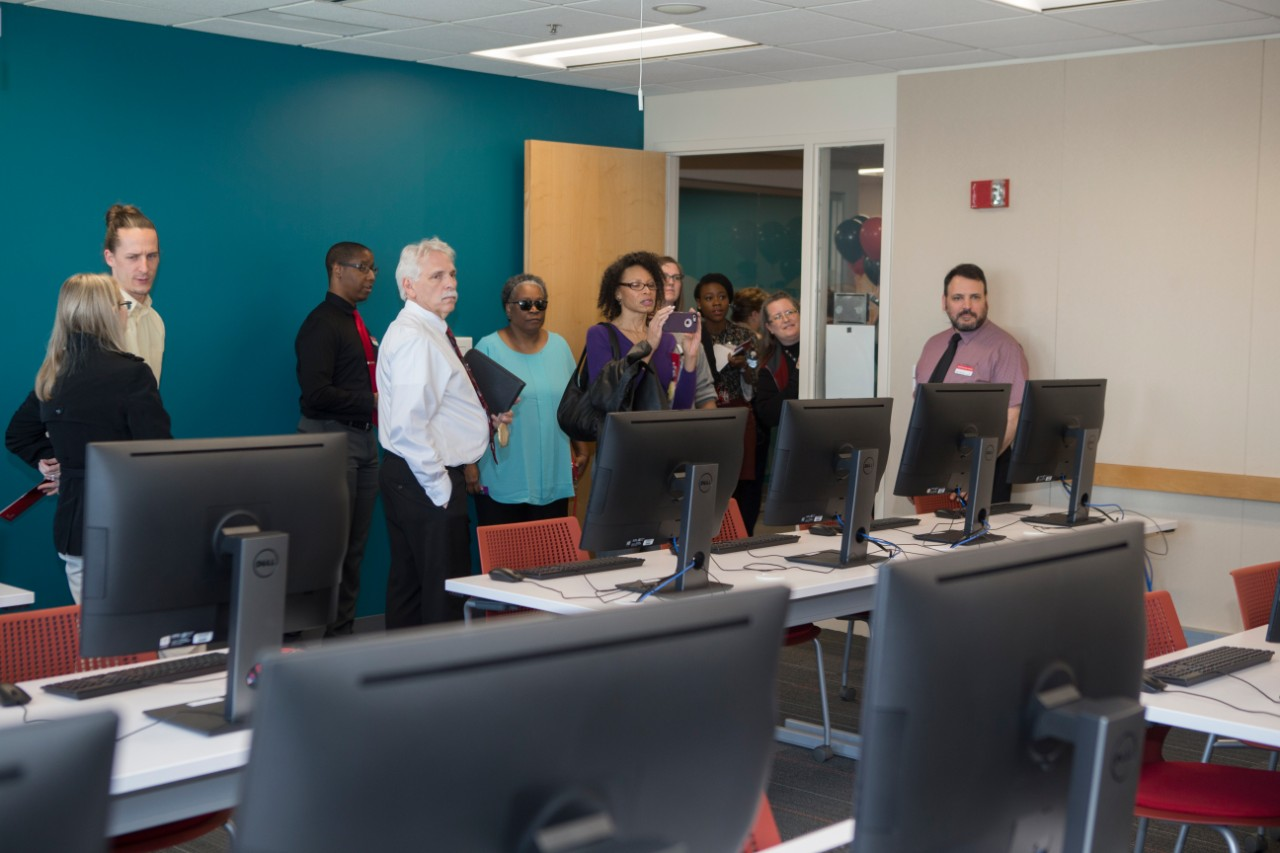 UC staff members stands inside a room of computers at the Staff Success Center ribbon cutting event.