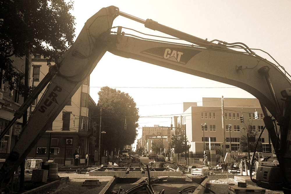 A Prus excavator bridges the trackwork for the diamond at 12th and Race Streets near Washington Park. (July 31, 2014)