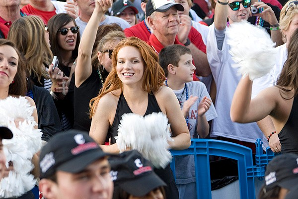 A member of UC's dance team cheers with fans at the Jackson Square pep rally.