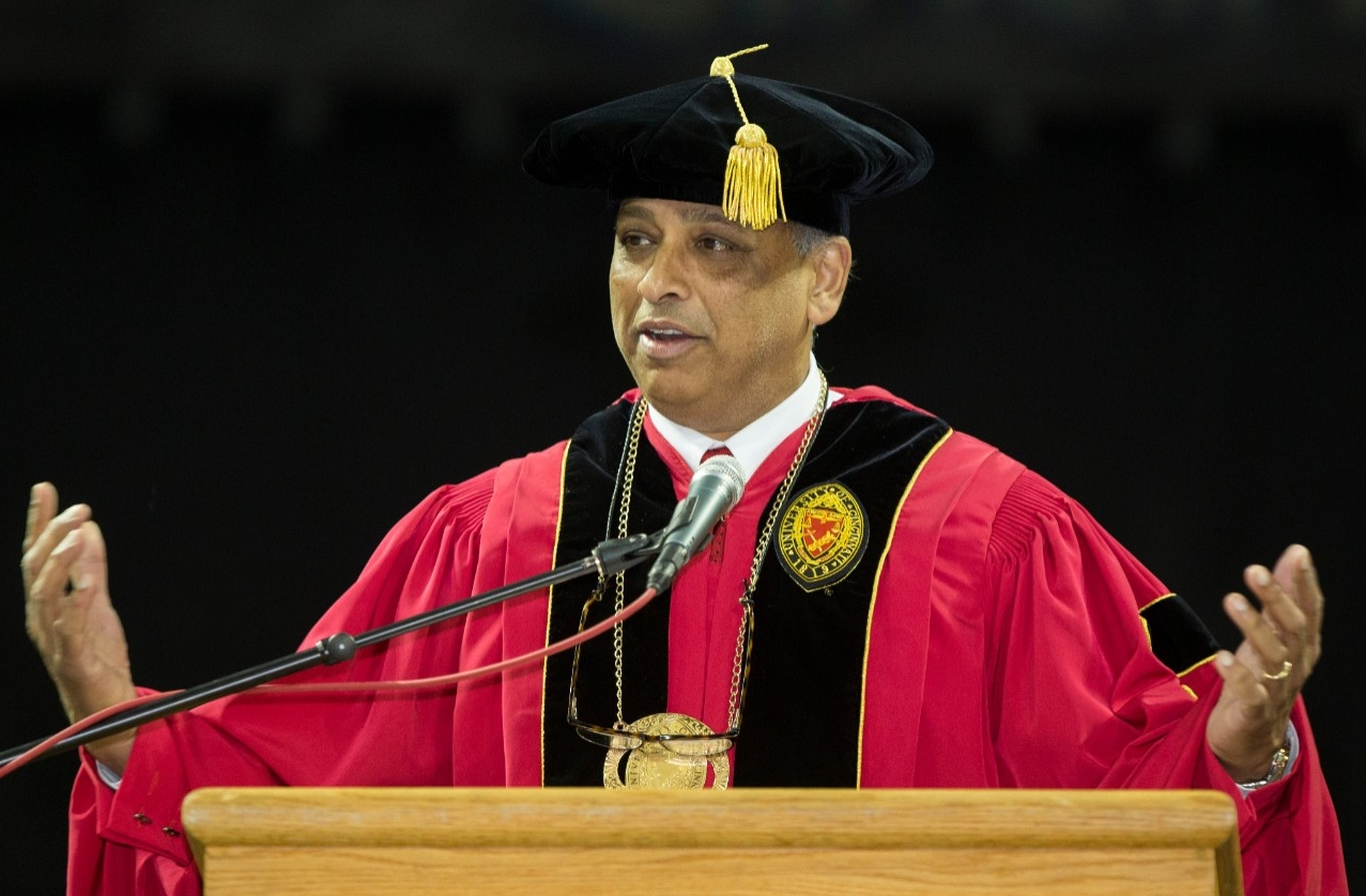 President Neville Pinto wears a black cap and red robe as he addresses the crowd at UC Commencement