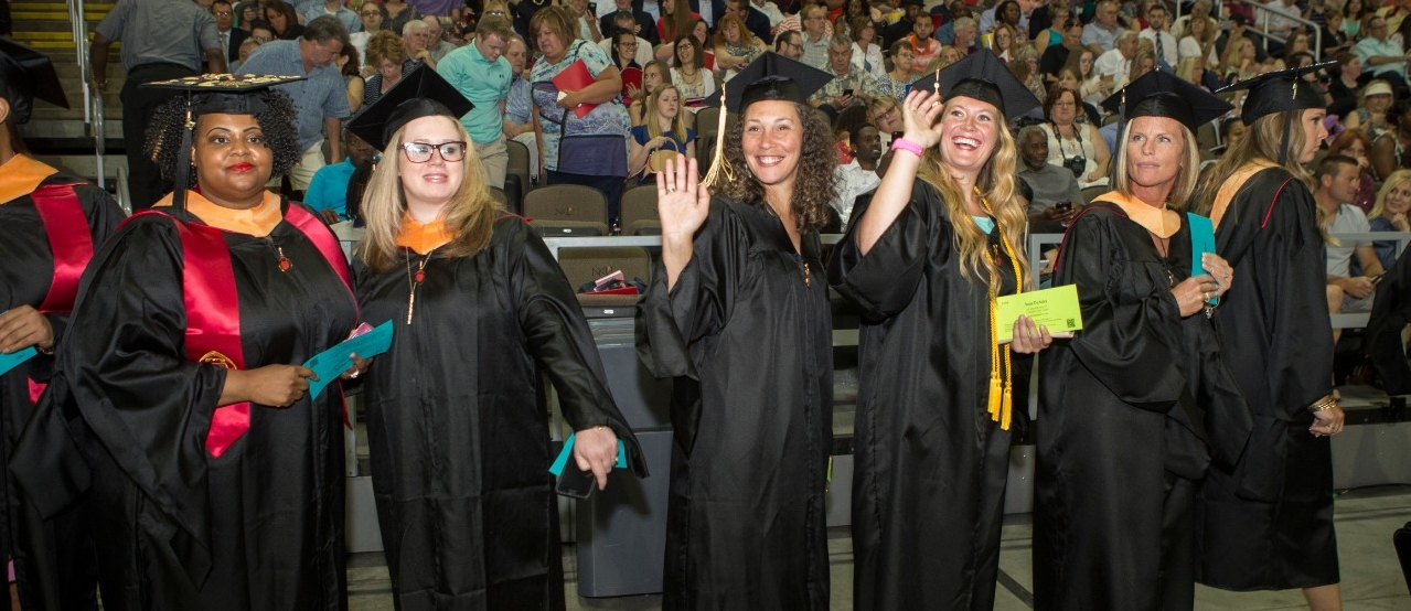 Female graduates in black caps and gowns smile at the audience during UC Commencement