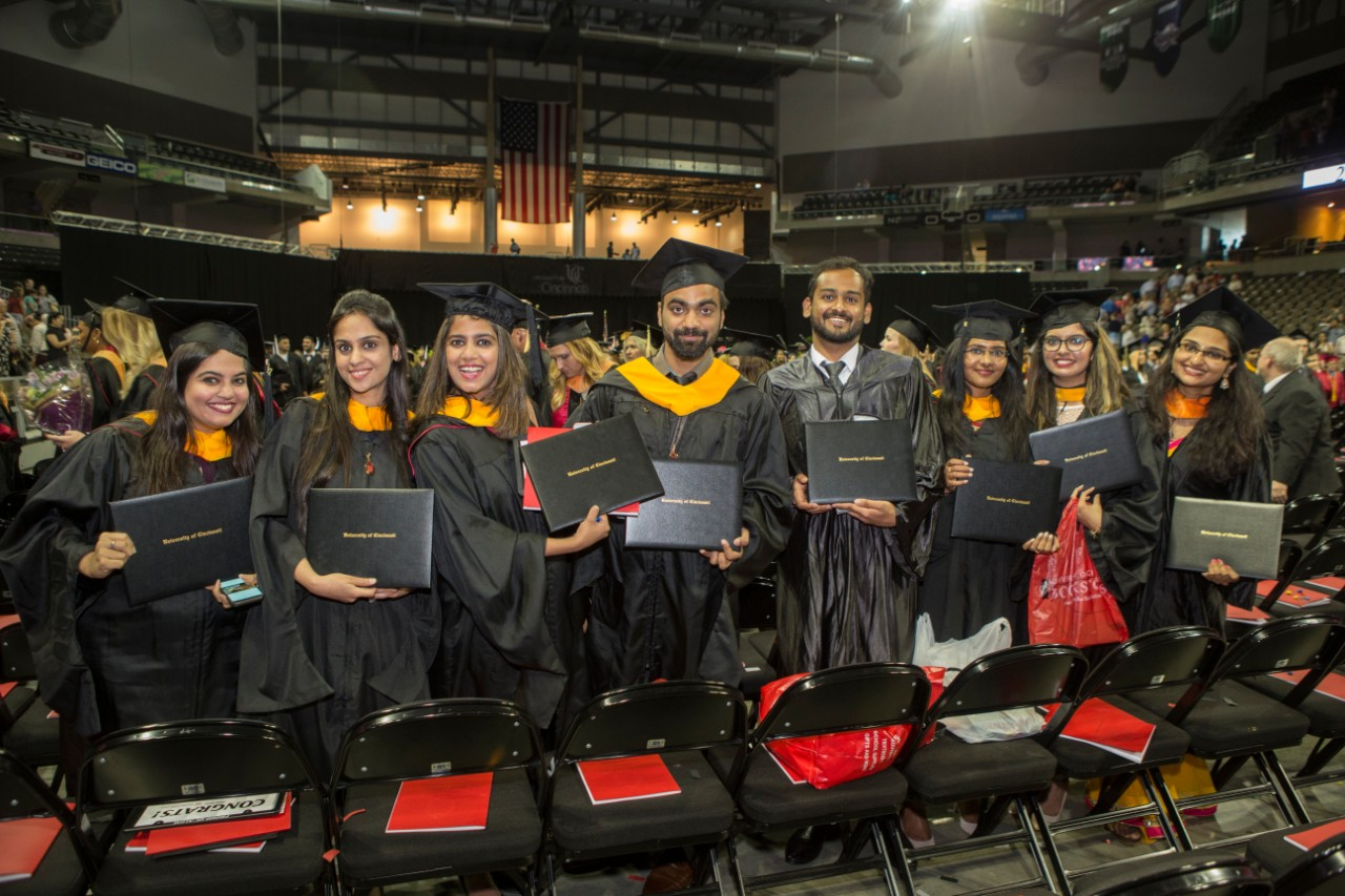 A row of graduates show off their new degrees at UC Commencement.