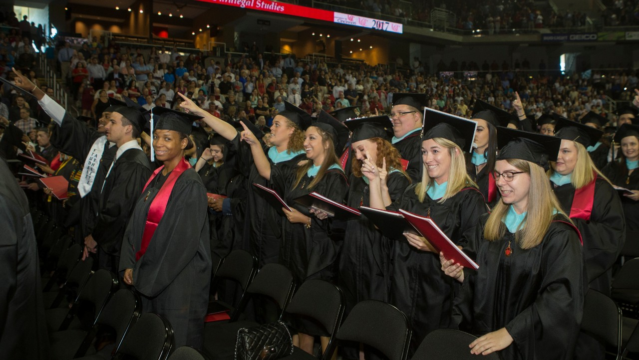 A crowd of graduates in black caps and gowns sing the alma mater at UC Commencement.