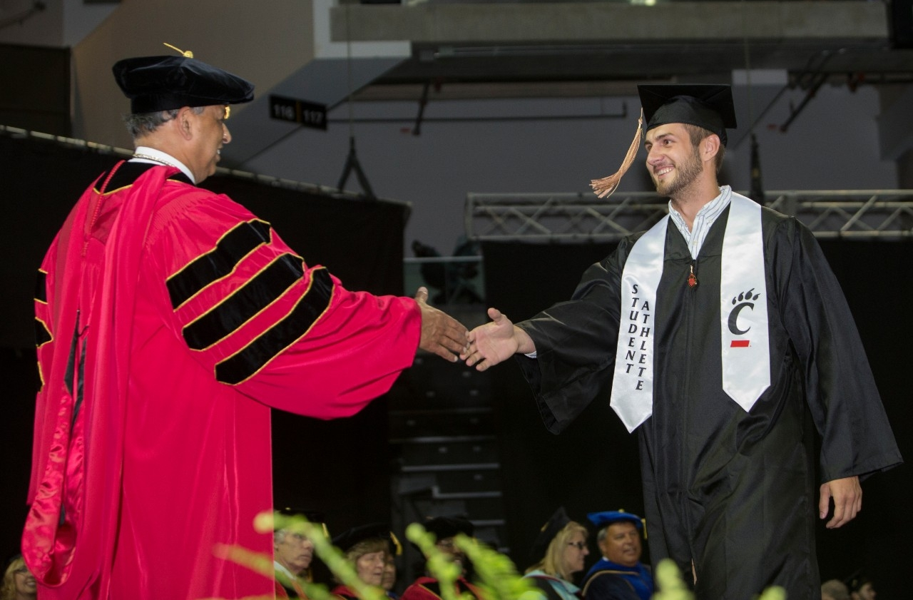 A student athlete graduate shakes president Pinto's hand on stage at UC Commencement.