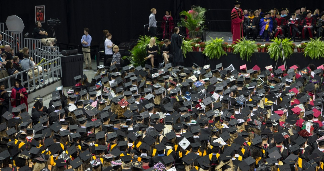 A sea of black graduation caps in an aerial shot at UC Commencement