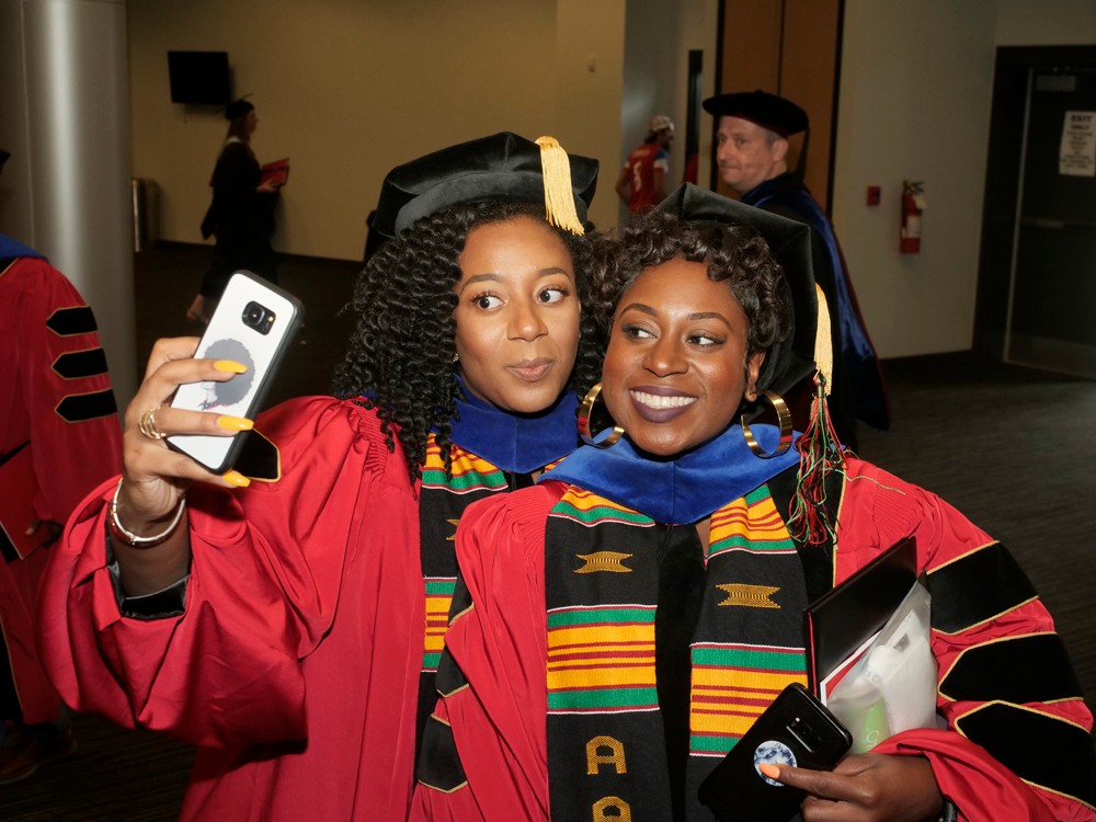 Two doctoral students take a selfie backstage at Commencement.