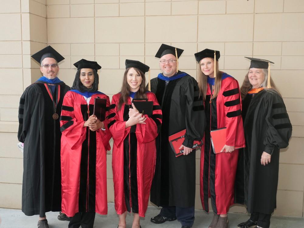 Six graduates pose outside.