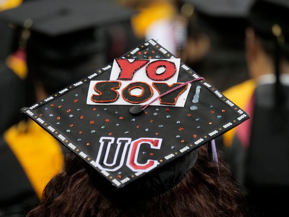 A student's mortarboard that reads Yo soy UC