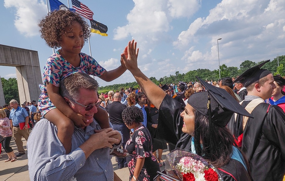 A graduate high fives a young girl riding on a man's shoulder's outside of BB&T Arena