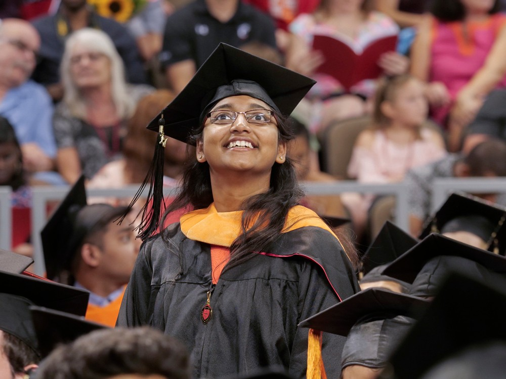 A graduate smiles and looks upward.