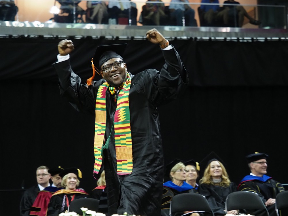 A graduate shakes his fists victoriously above his head as he crosses the dais.