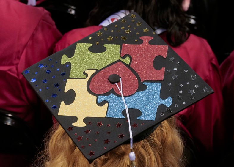 A graduate's mortarboard, decorated with an autism awareness icon.