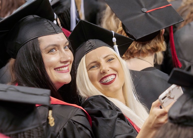 Two students smile into the crowd at Summer 2018 Commencement