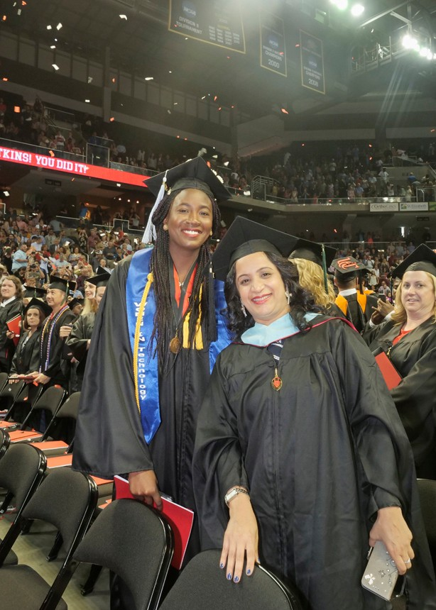 Two graduates pose for a photo.