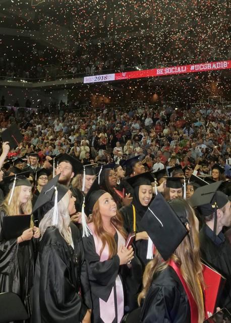 Confetti falls on the graduates.