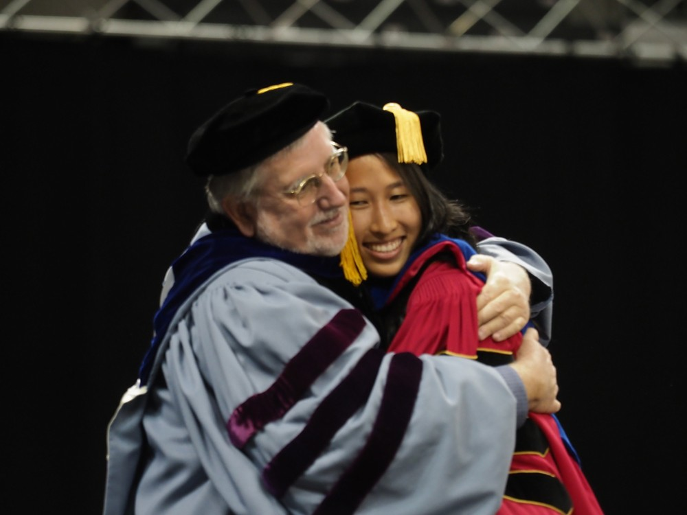 A student and faculty member share an embrace on the dais.
