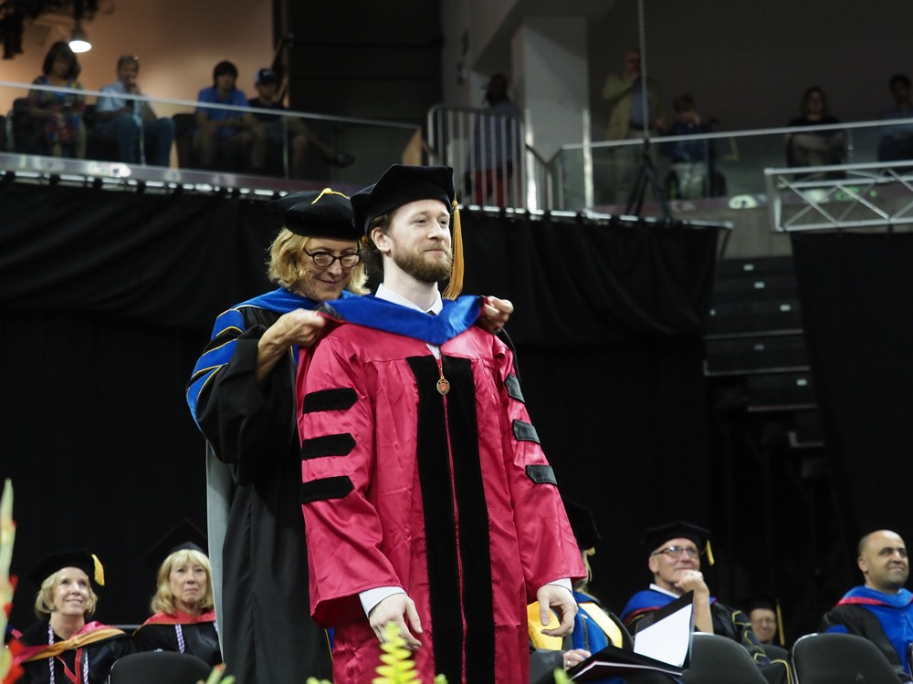 A graduate beams with pride while receiving his doctoral hood