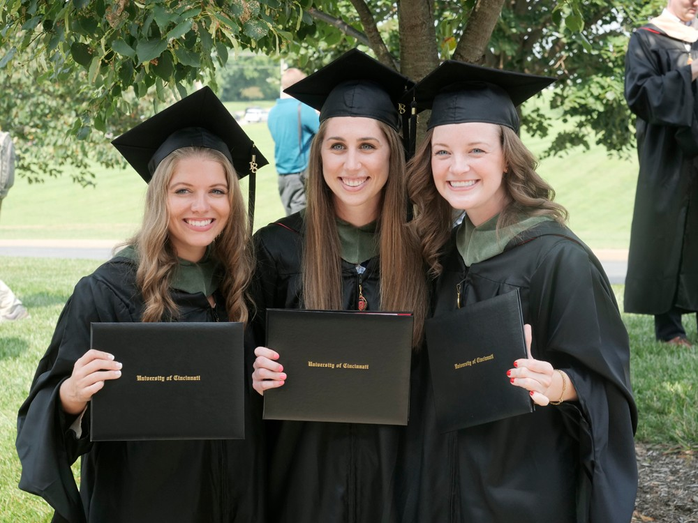 Three female students show off their diplomas outside of the arena.