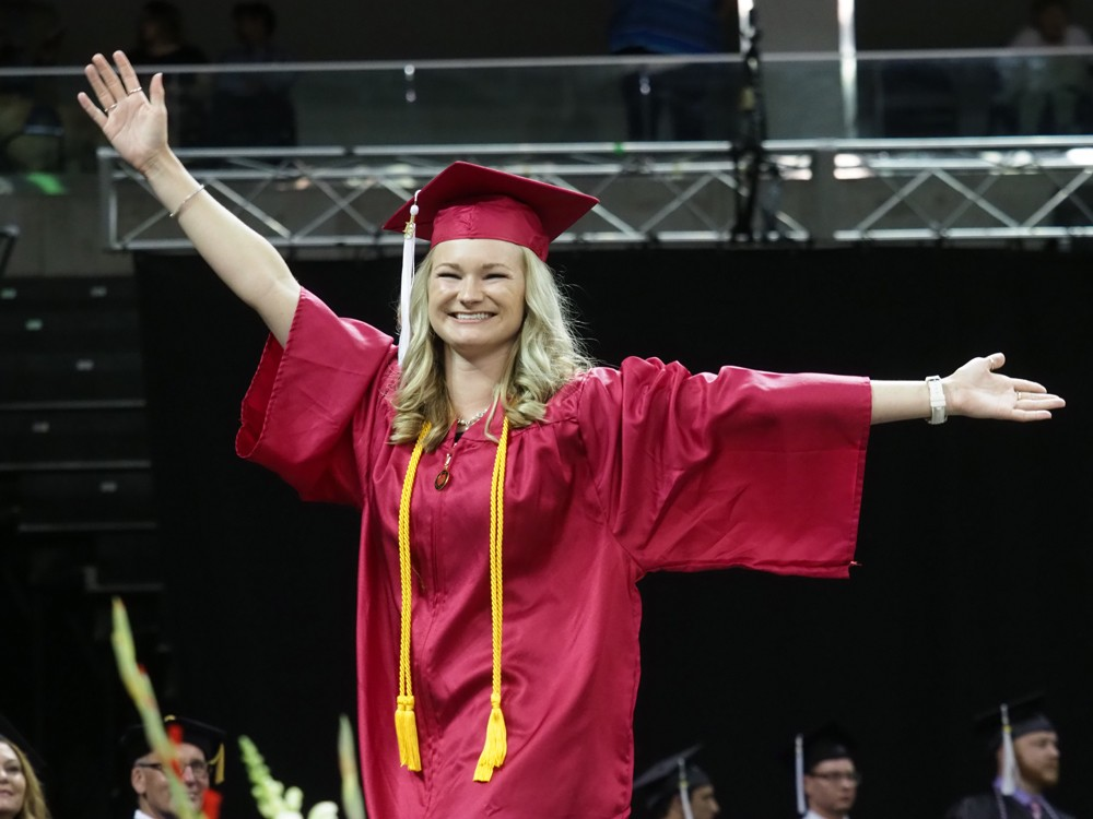 A student spreads her arms and smiles as she crosses the dais.