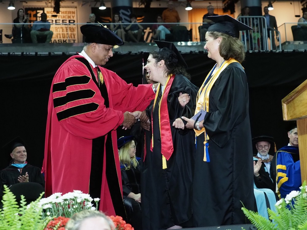 UC President Neville Pinto shakes hands with a graduate who crossed the dais with the assistance of friends.
