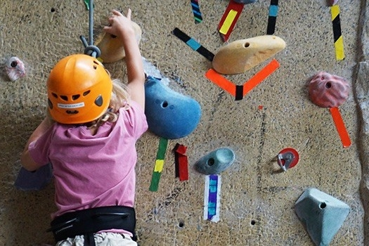 Child climbs the rock wall in UC's Rec Center during UC athletic summer camp.