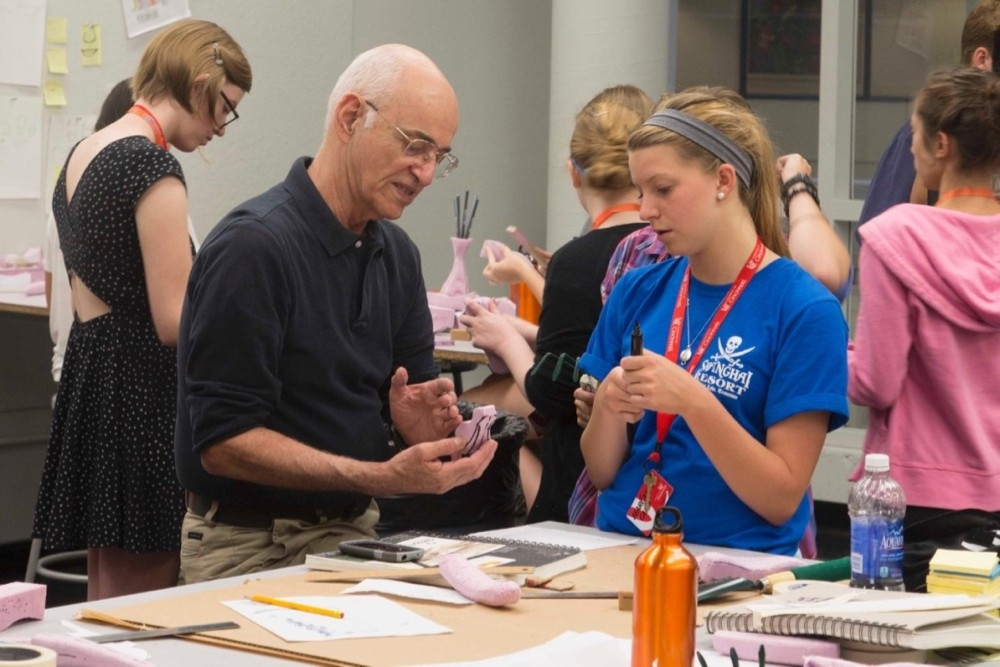 UC DAAP instructor works with a young UC DAAP summer camp artist.