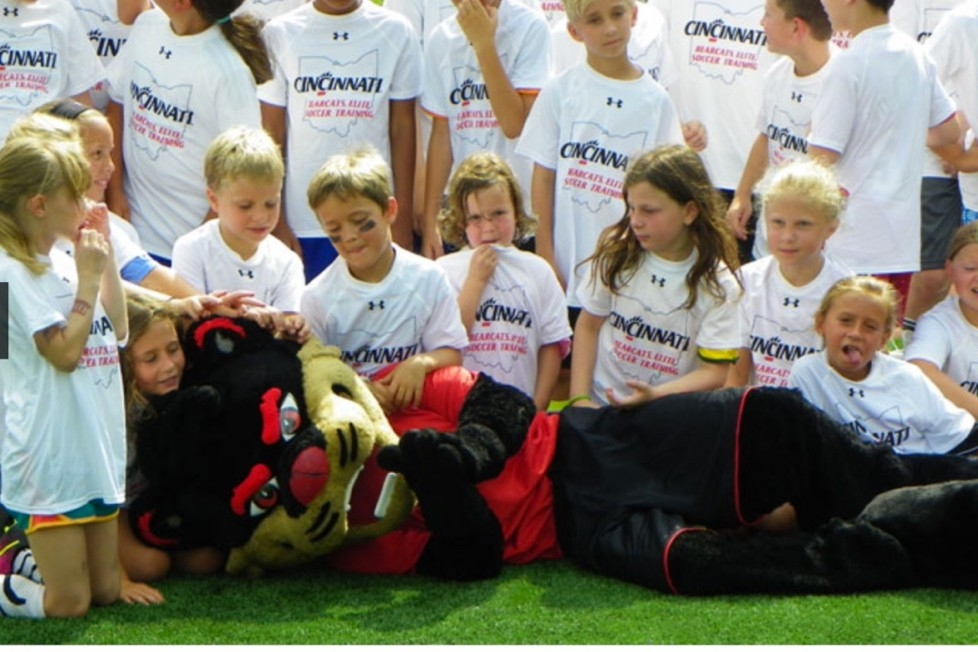 UC Bearcat lays in front of a group young soccer players at UC's athletic summer camp.