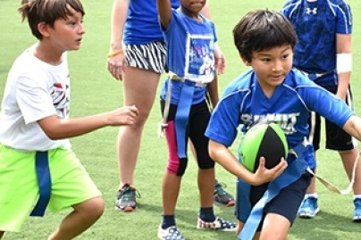 Children play flag football as part of UC football summer camp.