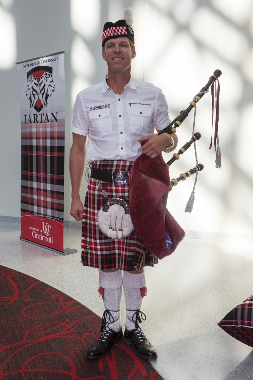 A bagpiper (Robert Reid) stands wearing a kilt and holding bagpipes